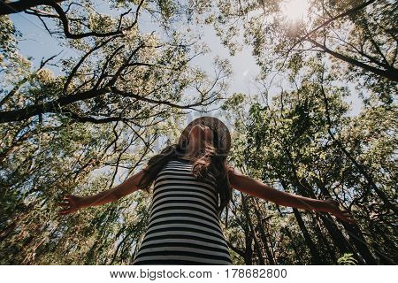 Woman enjoying and breathing deeply in a eucalyptus tree forest. Australia.