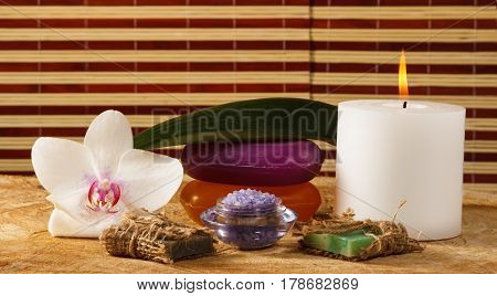 Spa products with white orchid flower bowl with sea salt handmade soap candle on wooden board