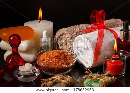 Spa products with soap bowls with sea salt bottles with aromatic oil candles and towels on black background