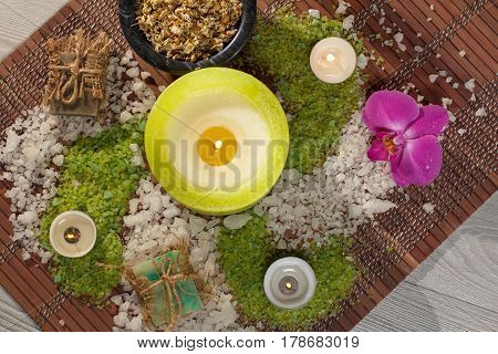 Spa accessories with soap red orchid flower bowl with dried chamomile flowers bottles with aromatic oil sea salt candles on bamboo napkin