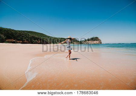 Happy woman dancing and enjoying Australian beach.