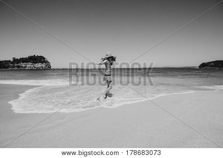 Black and white portrait of woman enjoying and dancing in the beach.
