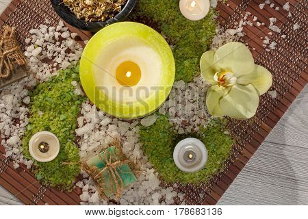 Spa accessories with soap yellow orchid flower bowl with dried chamomile flowers bottles with aromatic oil sea salt candles on bamboo napkin