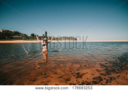 Woman splashing out water with the hands at the beach in Australia.