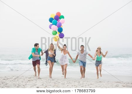 Group of happy friends running on the beach with multicolored balloons