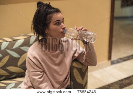 Beautiful Girl. Girl With A Bottle Of Water On The Armchair.