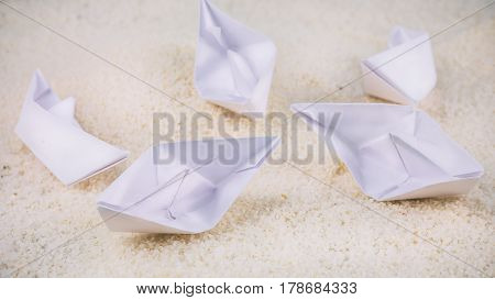 Without Leader. Paper Ships Chaotic Laying on Sandy in the Desert.