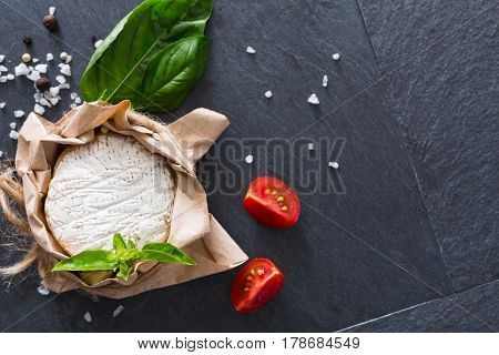 Camembert or brie circle cheese in brown kraft paper decorated with basil and pieces of cherry tomatoes, top view image with copy space on black stone desk surface