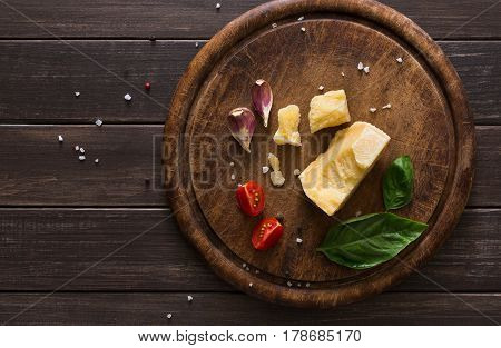 Cheese delikatessen closeup on rustic wood. Wooden desk with parmesan, camembert cuts decorated with garlic, tomato and basil, top view image