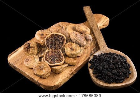 Dried figs on wooden chopping board and black raisins in wooden spoon on black background