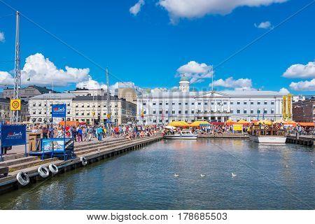 HELSINKI FINLAND - JULY 19 2016: Many people enjoy a summers day on a Market Square near Helsinki harbour