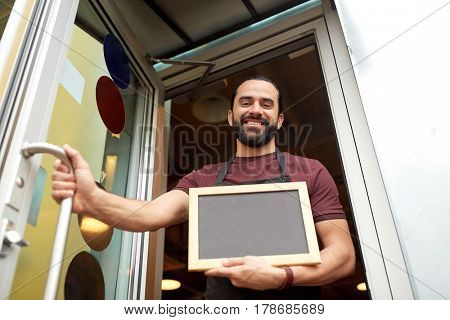 small business, people and service concept - happy man or waiter with blackboard at bar or restaurant entrance door