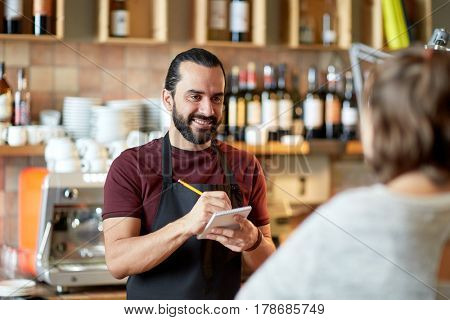 small business, people and service concept - happy man or waiter with notebook and pencil serving customer at coffee shop or bar