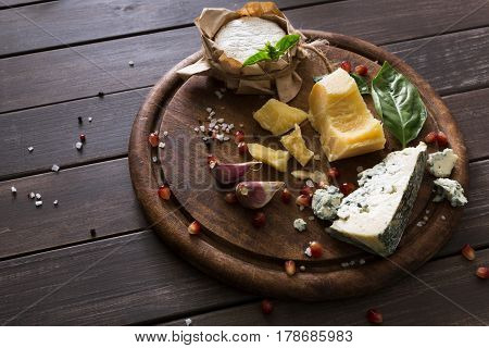 Cheese delikatessen on rustic wood. Blue cheese roquefort, parmesan, camembert and brie cuts decorated with garlic, pomegranate and basil, french cuisine ingredients