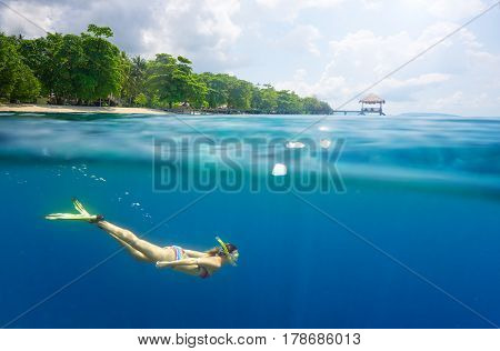 snorkeling in clear tropical waters in near of exotic island summer. Beach holiday vacation woman