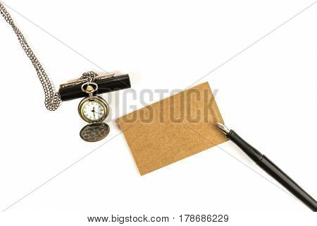 An overhead photo of a kraft paper business card with an ink pen and a vintage chain watch on a white background. A mockup or a minimalist banner with copy space