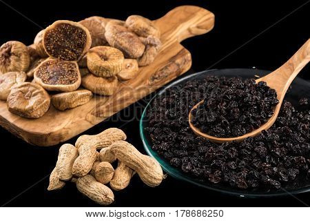 Dried figs on wooden chopping board peanuts and black raisins in plate on black background