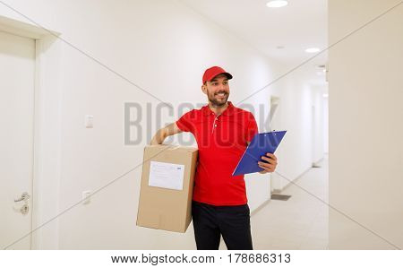 delivery, mail, people and shipment concept - happy man in red uniform with parcel box and clipboard in corridor