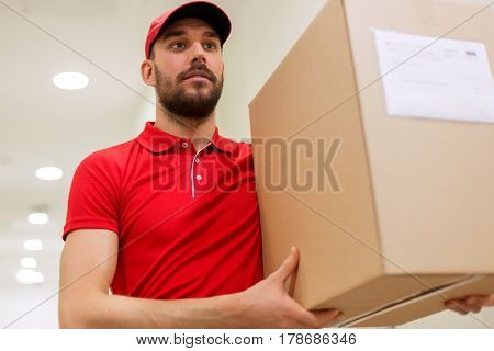 delivery, mail, people and shipment concept - man in red uniform with parcel box in corridor