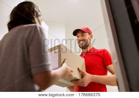delivery, mail, people and shipping concept - happy man delivering parcel box to customer home