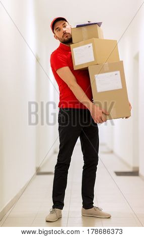 delivery, mail, people and shipment concept - man in red uniform with parcel boxes and clipboard in corridor