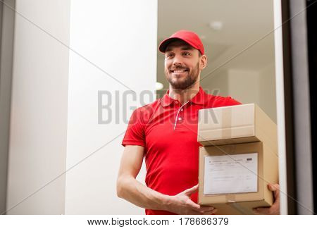 delivery, mail, people and shipment concept - happy man in red uniform with parcel boxes in corridor at open customer door