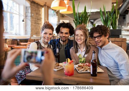 technology, lifestyle and people concept - happy friends with smartphone photographing at bar or cafe
