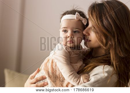 Young mother holding and hugging her baby girl. Focus on the baby