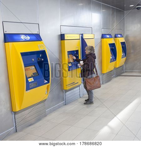 Utrecht Netherlands 15 march 2017: woman buys ticket at machine on utrecht central railway station in the netherlands