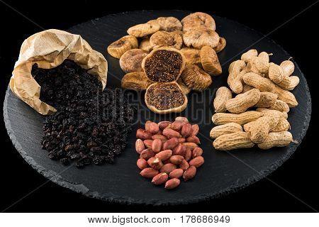 Dried figs peanuts and black raisins on black dish