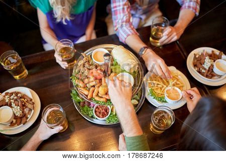 leisure, food, drinks, people and holidays concept - friends eating snack and drinking beer at bar or pub