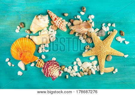An overhead photo of a sea star, sea shells, and pebbles forming a frame on a vibrant turquoise background, with a place for text inside. A design template for a summer vacation banner