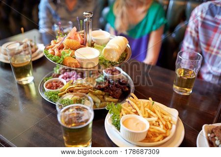leisure, food, drinks and holidays concept - people sitting at table with food and beer glasses at bar or pub