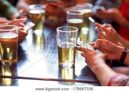 people, leisure, technology and drinks concept - friends drinking beer and texting on smartphones at bar or pub