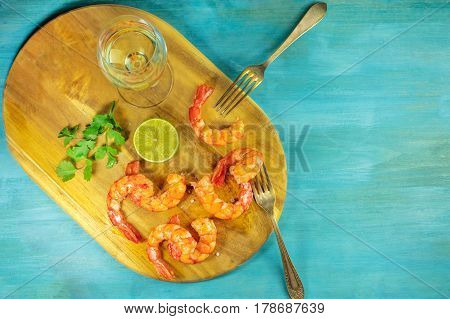 An overhead photo of a glass of white wine with cooked shrimps, a slice of lime, cilantro leaves, salt flakes, and plenty of copy space, on a vibrant blue background