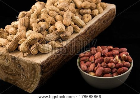 Peanuts in nutshell on a piece of wood and peeled peanuts in white bowl on black background