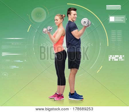 sport, fitness, technology and people concept - happy sportive man and woman with dumbbells flexing muscles over green background