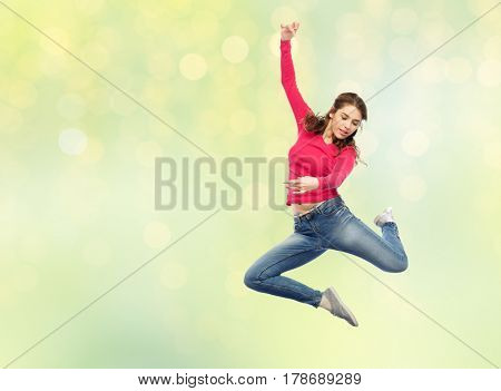 happiness, freedom, motion and people concept - smiling young woman jumping in air over summer green lights background