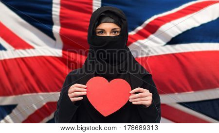 love, charity, immigration, valentines day and people concept - muslim woman in hijab holding red heart over british flag background