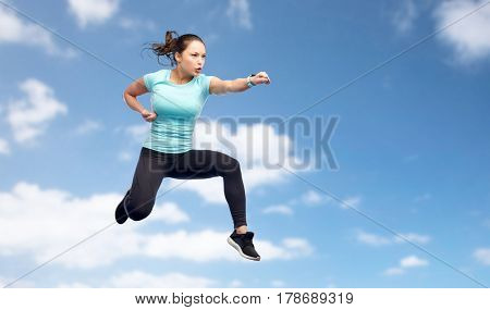 sport, fitness, motion and people concept - happy young woman jumping in air in fighting pose over blue sky background