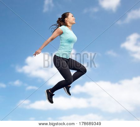 sport, fitness, motion and people concept - happy smiling young woman jumping in air over blue sky and clouds background