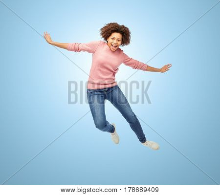 people, motion and action concept - happy african american young woman jumping over blue background
