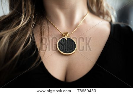Chakra medallion hanging on the woman's neckline, made of alloy of many minerals, piece of meteorite and golden frame.