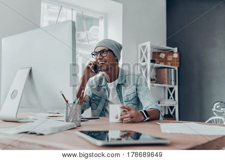 Good talk with client. Handsome young man in eyewear talking on smart phone and smiling while sitting at his working place in creative office
