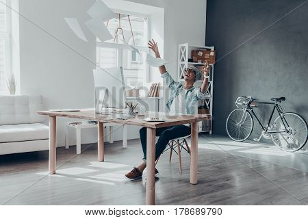 Feeling so happy! Handsome young man throwing paper in air and smiling while sitting at his working place in creative office