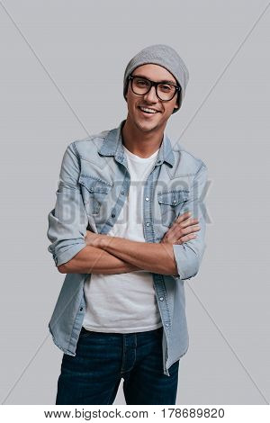 Young and carefree. Good looking young man in jeans shirt and headwear keeping arms crossed and looking at camera with smile while standing against grey background