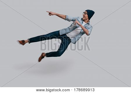 Pointing copy space in mid-air. Full length of handsome young man in jeans shirt gesturing and smiling while jumping against grey background