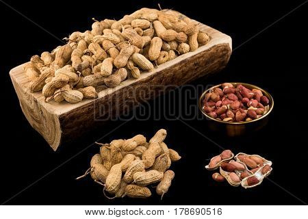 Peanuts in nutshell on a piece of wood and peeled peanuts in golden bowl on black background