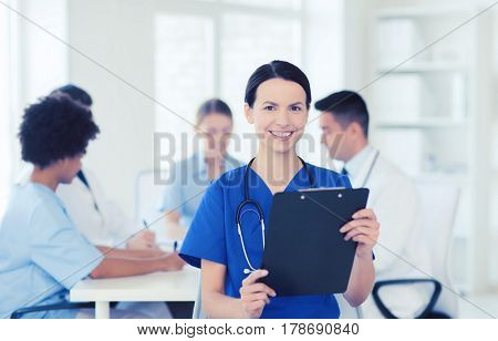 clinic, profession, people and medicine concept - happy female doctor with clipboard over group of medics meeting at hospital