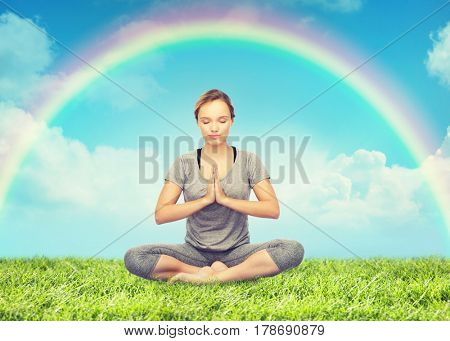 fitness, people, harmony and healthy lifestyle concept - woman making yoga meditation in lotus pose over grass and rainbow in blue sky background